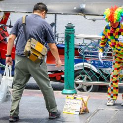 Un hombre le da dinero a un artista callejero en Bangkok el 28 de mayo de 2020. (Foto de Mladen ANTONOV / AFP) | Foto:AFP