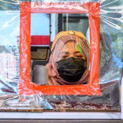 Un vendedor con una máscara facial y un escudo vende bebidas detrás de una pantalla de plástico protectora en Bangkok el 28 de mayo de 2020, ya que los sectores de la economía se están reabriendo después de las restricciones para detener la propagación del coronavirus COVID-19. (Foto por Mladen ANTONOV / AFP) | Foto:AFP