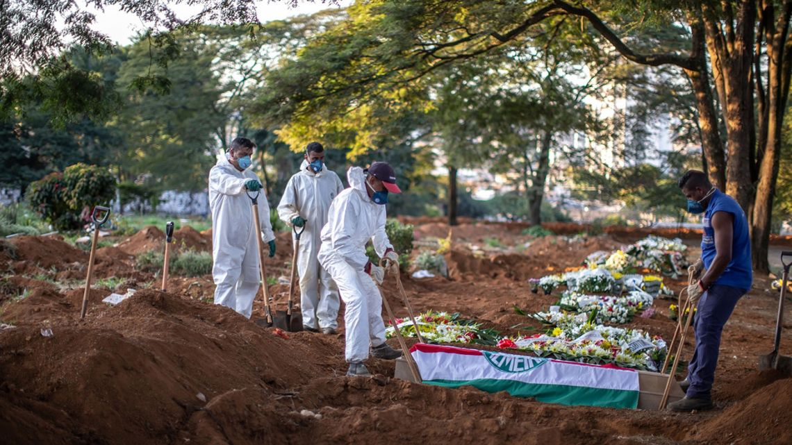 Workers wearing protective gear lower the casket of a Covid-19 victim at the Vila Formosa cemetery in São Paulo, Brazil, on Wednesday, April 29, 2020. Brazilians are resuming a measure of normal life just as Covid-19 deaths are spiking to hundreds per day, turning their country into a global hotspot.