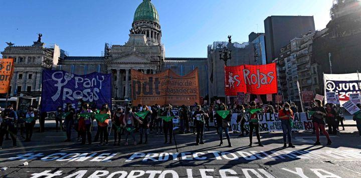 Las mujeres levantan pañuelos verdes para exigir la legalización del aborto fuera del edificio del Congreso durante el II Día Internacional de Acción para la Salud de la Mujer en Buenos Aires, el 28 de mayo de 2020, en medio de la nueva pandemia de coronavirus. - El aborto en Argentina está permitido solo en casos de violación o si la salud de la madre está en peligro. Los pañuelos verdes son un símbolo de la lucha de las mujeres para legalizar el aborto. (Foto por JUAN MABROMATA / AFP)
