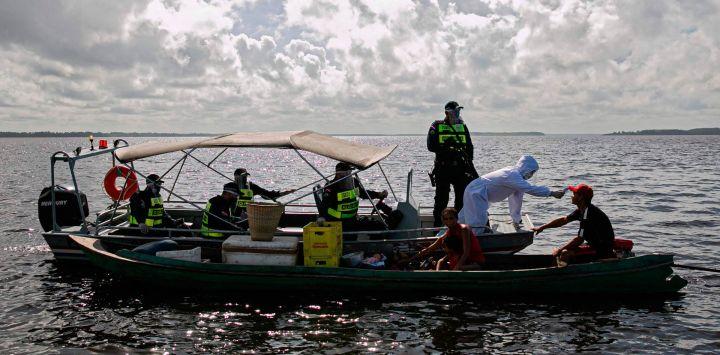Un trabajador médico del gobierno, en una operación conjunta con la policía militar, revisa a un pasajero en un bote en la bahía de Melgaco, al suroeste de la isla de Marajo, estado de Pará, Brasil, el 27 de mayo de 2020. - Personas a bordo de pequeñas embarcaciones, transbordadores y A los barcos en el río se les revisó la temperatura corporal mientras las autoridades intentaban combatir el nuevo coronavirus. (Foto por TARSO SARRAF / AFP)