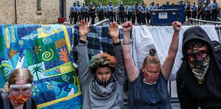 Los manifestantes levantan las manos mientras lloran por los gases lacrimógenos durante una manifestación en un llamado a la justicia para George Floyd después de su muerte, fuera del 3er Recinto Policial el 27 de mayo de 2020 en Minneapolis, Minnesota. - La familia de un hombre afroamericano asesinado por la policía de Minneapolis mientras estaba bajo custodia exigió el miércoles que los oficiales sean acusados de asesinato. Después de una noche de protestas furiosas por la muerte de George Floyd, con la policía disparando gases lacrimógenos y balas de goma en la ciudad del norte de los EE. UU., Su hermana Bridgett Floyd exigió el arresto de los cuatro policías blancos involucrados en su muerte. (Foto por Kerem Yucel / AFP)