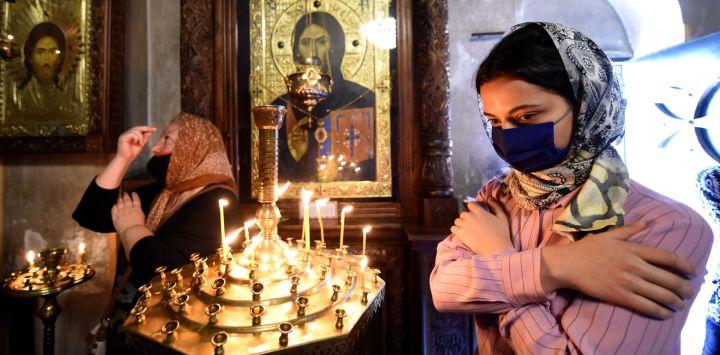 Las mujeres que usan una máscara facial oran durante el servicio de la iglesia ortodoxa 'Ascensión del Señor' en una catedral en Tbilisi el 28 de mayo de 2020, en medio del brote de COVID-19 causado por el nuevo coronavirus. (Foto por Vano Shlamov / AFP)