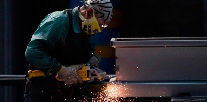 Un empleado trabaja en la fabricación de ataúdes de acero en la Platinum Casket Company en Los Reyes Acaquilpan, México, el 28 de mayo de 2020, en medio de la nueva pandemia de coronavirus. - La compañía diseñó los ataúdes como una alternativa para las familias de las víctimas de COVID-19 que prefieren enterrar a sus fallecidos. El ataúd está hecho de acero, tiene forma de cápsula y todas las paredes están selladas y soldadas para evitar fugas de líquidos. (Foto por CLAUDIO CRUZ / AFP)