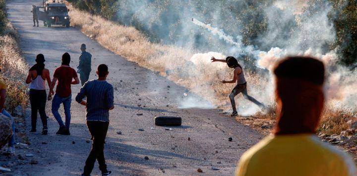 Un manifestante palestino devuelve un bote de gas lacrimógeno durante enfrentamientos con soldados israelíes en la ciudad de Tuqua en Cisjordania ocupada por Israel el 28 de mayo de 2020. (Foto de Musa Al SHAER / AFP)