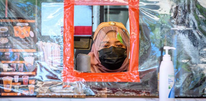 Un vendedor con una máscara facial y un escudo vende bebidas detrás de una pantalla de plástico protectora en Bangkok el 28 de mayo de 2020, ya que los sectores de la economía se están reabriendo después de las restricciones para detener la propagación del coronavirus COVID-19. (Foto por Mladen ANTONOV / AFP)