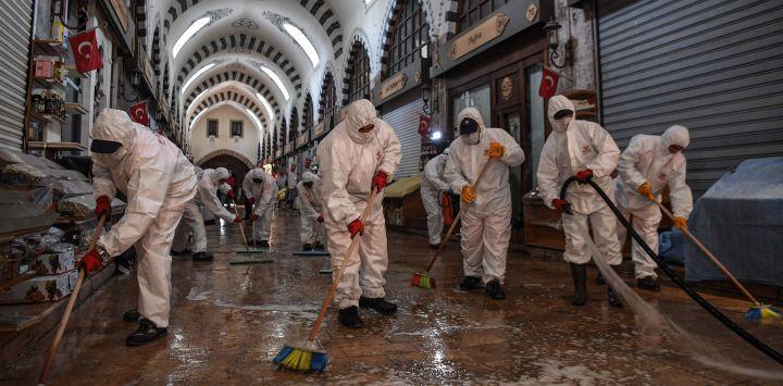 Los trabajadores del municipio de Fatih que usan equipo de protección personal (EPP) desinfectan el icónico Bazar de las Especias en Estambul para evitar la propagación del COVID-19 causado por el nuevo coronavirus, el 28 de mayo de 2020. (Foto de OZAN KOSE / AFP)
