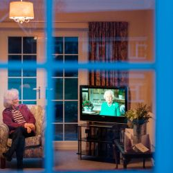 Valerie Cloke, sentada en un sillón en su sala de estar mirando televisión mientras la reina Isabel II de Gran Bretaña pronuncia un discurso especial en el pueblo de Hartley Wintney, al oeste de Londres, el 5 de abril de 2020 durante el cierre nacional debido a la pandemia de Coronavirus. - No ha salido de su casa desde que comenzó el cierre patronal en todo el país el 23 de marzo. Sus amigos y vecinos de la aldea la apoyan. (Foto de ADRIAN DENNIS / AFP) / AFP FOTO ENSAYO DE ADRIAN DENNIS | Foto:AFP