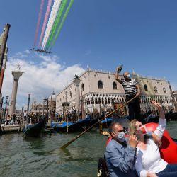 Personas que toman un paseo en góndola y una ola de gondolero mientras la unidad acrobática de la Fuerza Aérea Italiana Frecce Tricolori (Flechas Tricolored) se presenta el 29 de mayo de 2020 sobre Venecia como parte de la iniciativa militar aeronáutica  | Foto:AFP