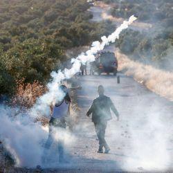 Un manifestante palestino devuelve un bote de gas lacrimógeno durante enfrentamientos con soldados israelíes en la ciudad de Tuqua en Cisjordania ocupada por Israel el 28 de mayo de 2020. (Foto de Musa Al SHAER / AFP) | Foto:AFP