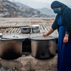 Una mujer religiosa evangélica agita una olla en un comedor de beneficencia de la sección de Pamplona Alta, que también sufre escasez de agua, en las afueras del sur de Lima el 28 de mayo de 2020, durante la nueva pandemia de coronavirus. (Foto de ERNESTO BENAVIDES / AFP) | Foto:AFP