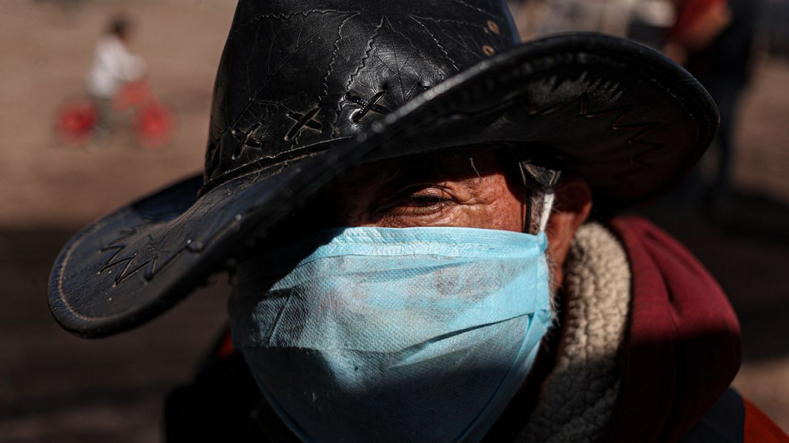 Hernaldo Gutíerrez, wearing a protective face mask, waits in line to receive free fruits and vegetables from produce vendors who are donating their time and products to those facing hardship because of lost income due to the new coronavirus pandemic, in Quillicura, on the outskirts of Santiago, Chile, Wednesday, April 29, 2020.