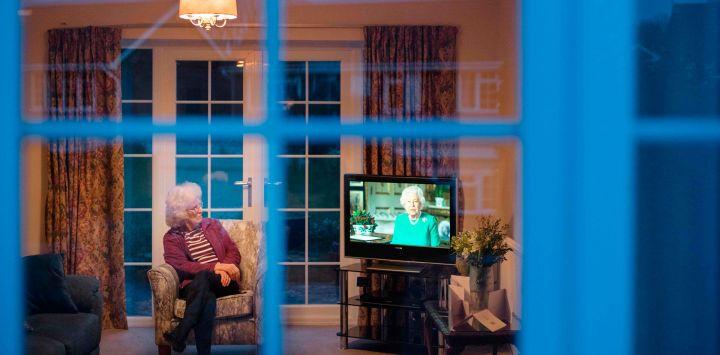 Valerie Cloke, sentada en un sillón en su sala de estar mirando televisión mientras la reina Isabel II de Gran Bretaña pronuncia un discurso especial en el pueblo de Hartley Wintney, al oeste de Londres, el 5 de abril de 2020 durante el cierre nacional debido a la pandemia de Coronavirus. - No ha salido de su casa desde que comenzó el cierre patronal en todo el país el 23 de marzo. Sus amigos y vecinos de la aldea la apoyan. (Foto de ADRIAN DENNIS / AFP) / AFP FOTO ENSAYO DE ADRIAN DENNIS