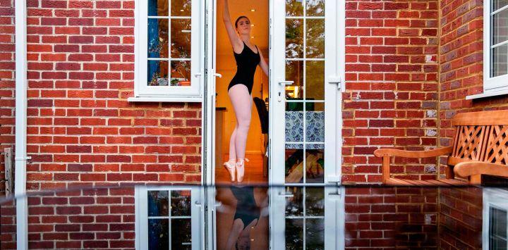 Lara Flux-Doble, de 17 años, baila en casa durante una clase de ballet en línea en Hartley Wintney, un pueblo a 45 millas al suroeste de Londres el 29 de abril de 2020 durante el cierre nacional debido a la nueva pandemia de coronavirus. - Flux-Doble actualmente estudia música, psicología y artes escénicas en Farnborough Sixth Form College y tiene clases de actuación en línea todos los días de la semana, que incluyen tap, ballet, piano y teatro musical. Ella aspira a trabajar en la industria del teatro o en el sector de la salud como fisioterapeuta o terapeuta vocal. (Foto de ADRIAN DENNIS / AFP).