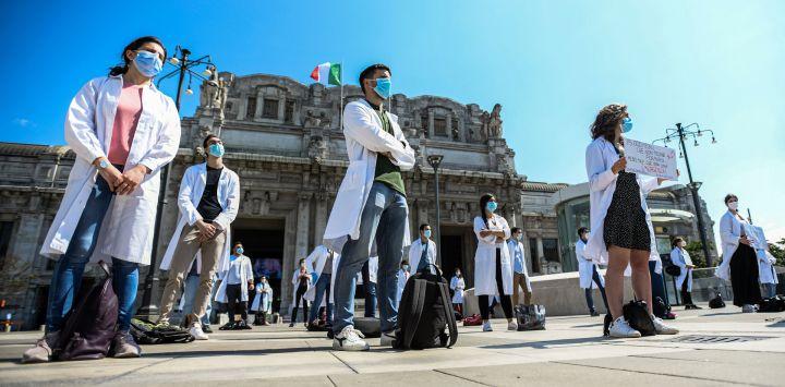 Estudiantes de medicina, médicos recién calificados y médicos en formación realizan una protesta frente a la estación central de trenes de Milán el 29 de mayo de 2020, solicitando una reforma educativa de la formación médica, a medida que el país alivia sus medidas de cierre encaminadas a frenar la propagación del COVID-19 infección, causada por el nuevo coronavirus. (Foto de Piero Cruciatti / AFP)