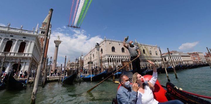 Personas que toman un paseo en góndola y una ola de gondolero mientras la unidad acrobática de la Fuerza Aérea Italiana Frecce Tricolori (Flechas Tricolored) se presenta el 29 de mayo de 2020 sobre Venecia como parte de la iniciativa militar aeronáutica