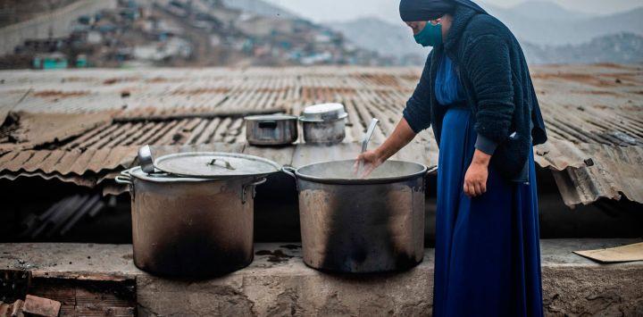 Una mujer religiosa evangélica agita una olla en un comedor de beneficencia de la sección de Pamplona Alta, que también sufre escasez de agua, en las afueras del sur de Lima el 28 de mayo de 2020, durante la nueva pandemia de coronavirus. (Foto de ERNESTO BENAVIDES / AFP)