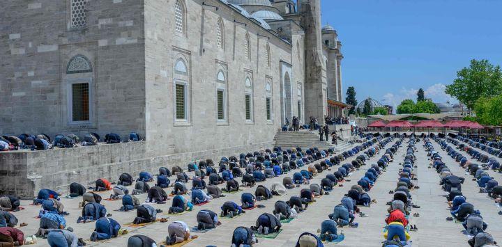 Los fieles con máscaras protectoras mantienen la distancia social requerida durante la oración del viernes frente a la Mezquita Fatih en Estambul el 29 de mayo de 2020, ahora abierta para oraciones, en medio del brote de COVID-19, causado por el nuevo coronavirus. - Los fieles en Turquía celebraron sus primeras oraciones comunales los viernes en 74 días después de que el gobierno reabrió algunas mezquitas como parte de sus planes para aliviar las medidas tomadas para combatir el brote de coronavirus. Las oraciones se llevaban a cabo en los patios de algunas mezquitas, para minimizar el riesgo de infección. (Foto por BULENT KILIC / AFP)