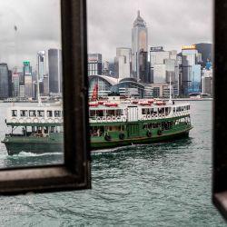 Se ve un ferry entrando en el muelle a través de la ventana de la terminal de ferry del puerto de Victoria en Hong Kong. | Foto:ISAAC LAWRENCE / AFP