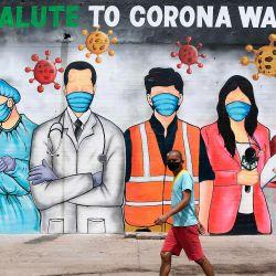 Un hombre con una máscara facial pasa junto a un mural en un basurero que dice 'un gran saludo a los guerreros de la corona' después de que el gobierno alivió un bloqueo nacional impuesto como medida preventiva contra el coronavirus COVID-19, en Nueva Delhi. | Foto:Sajjad Hussain / AFP
