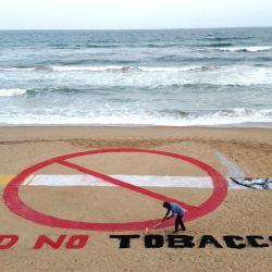 El artista indio Sudarsan Pattnaik crea una escultura de arena en la víspera del Día Mundial Sin Tabaco en la playa de Puri, a unos 65 km de Bhubaneswar. | Foto:AFP