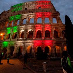 La gente camina frente al Coliseo iluminado con los colores de la bandera italiana en Roma.  | Foto:Tiziana Fabi / AFP