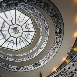 Un asistente del museo se encuentra en la Escalera de Bramante en el Museo del Vaticano que se abre de nuevo al público, mientras que en la ciudad el estado alivia su bloqueo para frenar la propagación de la infección por COVID-19, causado por el nuevo coronavirus. | Foto:ANDREAS SOLARO / AFP