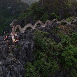 Esta fotografía muestra a los turistas en la cima de la montaña del Dragón en el punto de vista de las Cuevas de Mua en la provincia de Ninh Binh de Vietnam. | Foto:Manan Vatsyayana / AFP