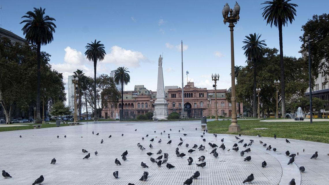 Pigeons take advantage of the lack of people in the Plaza de Mayo, with the Casa Rosada behind.