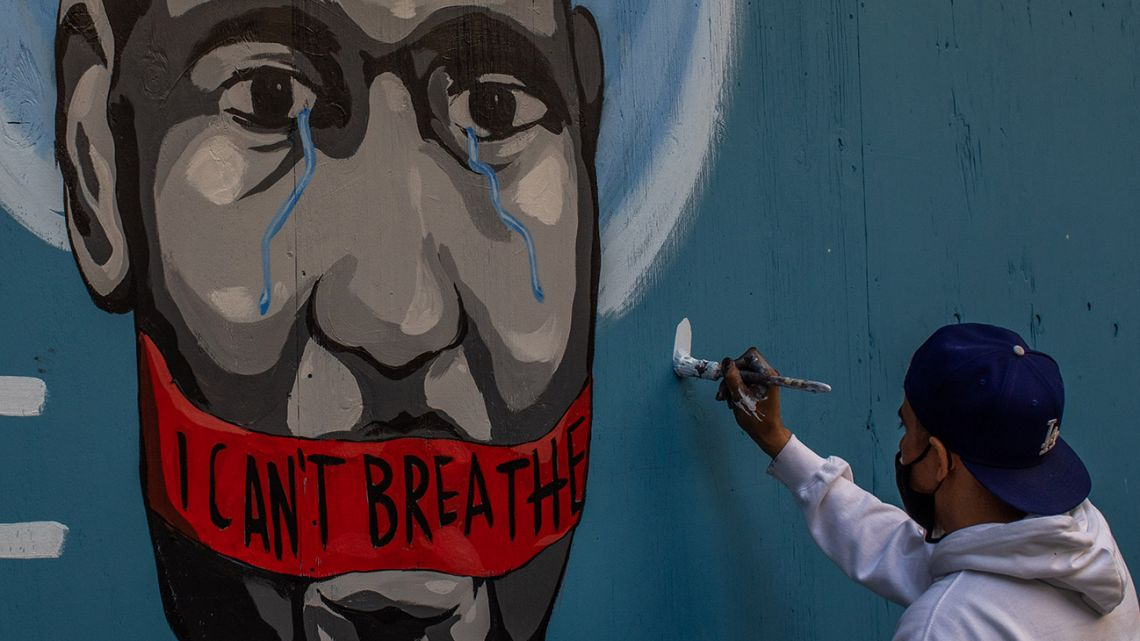 The artist Celos paints a mural in Downtown Los Angeles on May 30, 2020 in protest against the death of George Floyd, an unarmed black man who died while while being arrested and pinned to the ground by the knee of a Minneapolis police officer.