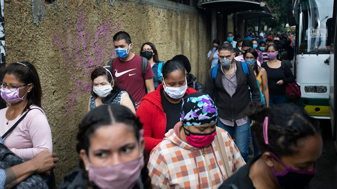 Pedestrians and commuters wearing face masks amid the new coronavirus pandemic crowd a sidewalk near a bus stop in Caracas, Venezuela, Monday, June 1, 2020. After two and a half months of Covid-19 related quarantine, some industries are allowed to reactivate under a scheme of five days' work and 10 days rest.