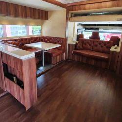El salón ofrece una mesa, un sillón y un televisor de 32 pulgadas.