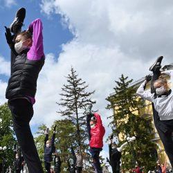 Los jóvenes atletas de la escuela de gimnasia rítmica, encabezados por Irina Deryugina, entrenadora principal del equipo ucraniano de gimnasia rítmica, usan máscaras protectoras y guantes, en medio de la pandemia continua de coronavirus COVID-19, mientras actúan durante la sesión de entrenamiento al aire libre.   Foto:Sergei Supinsky / AFP