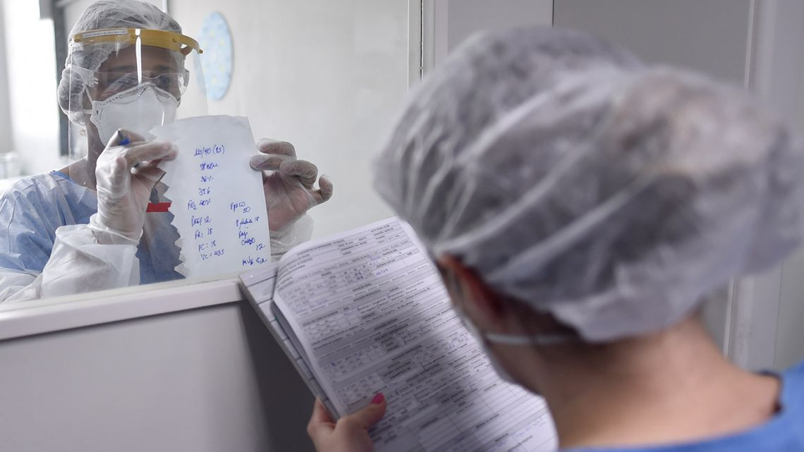 A health professional wearing full PPE (personal protective equipment) as a precautionary measure against the novel coronavirus, passes information about a COVID-19 patient through a window at the Intensive Care Unit (ICU) of the Santa Casa hospital in Belo Horizonte, state of Minas Gerais, Brazil, on June 1, 2020. The pandemic has killed 373,439 people worldwide since it surfaced in China late last year, according to an AFP tally at 1900 GMT on Monday, based on official sources. In a grim new landmark, infections in Latin America and the Caribbean surge past one million.