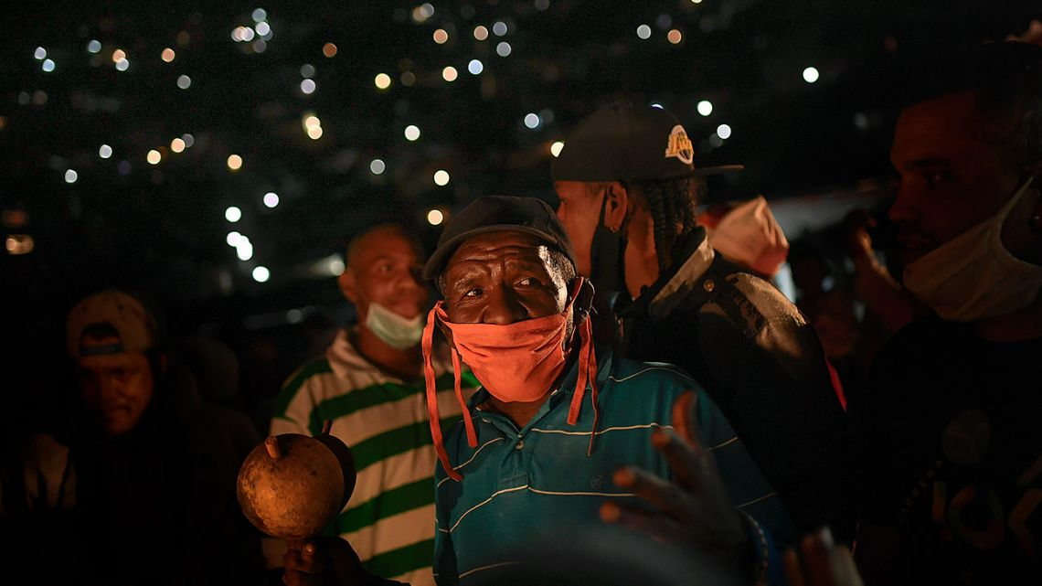 A man wearing a face mask amid the new coronavirus pandemic sings and prays during an overnight, Catholic religious procession in the San Agustín neighbourhood of Caracas, Venezuela.