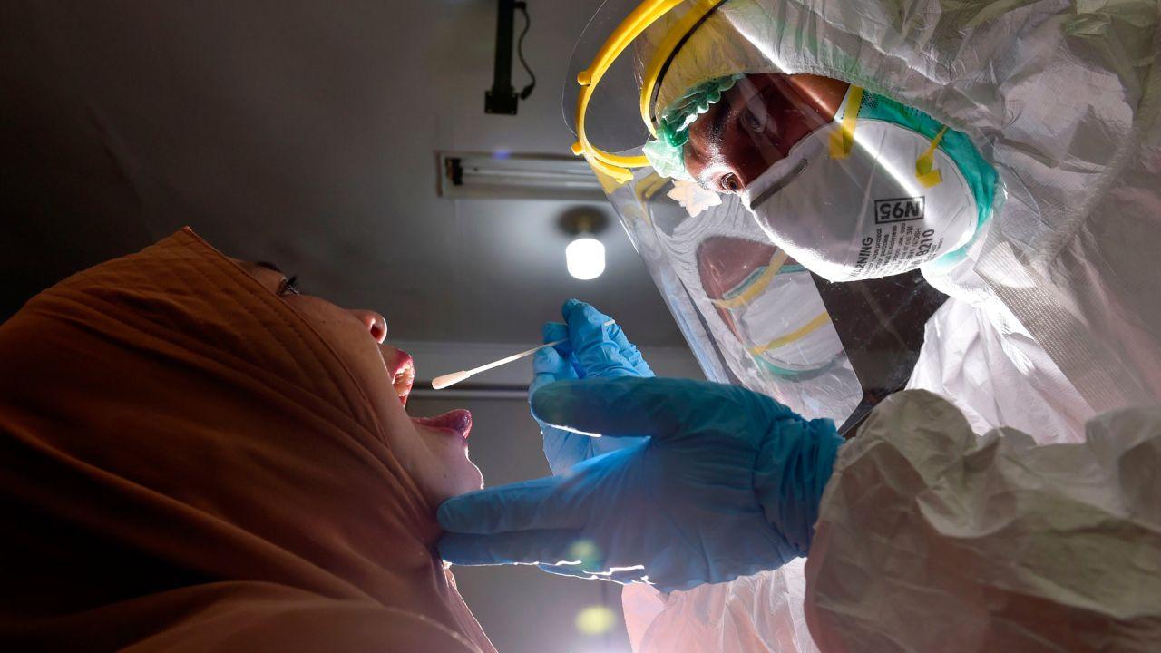 Indonesia. Un miembro del personal médico que usa equipo de protección personal recolecta una muestra de hisopo para evaluar el coronavirus COVID-19 de un empleado del gobierno en una oficina municipal en Banda Aceh.   Foto:CHAIDEER MAHYUDDIN / AFP