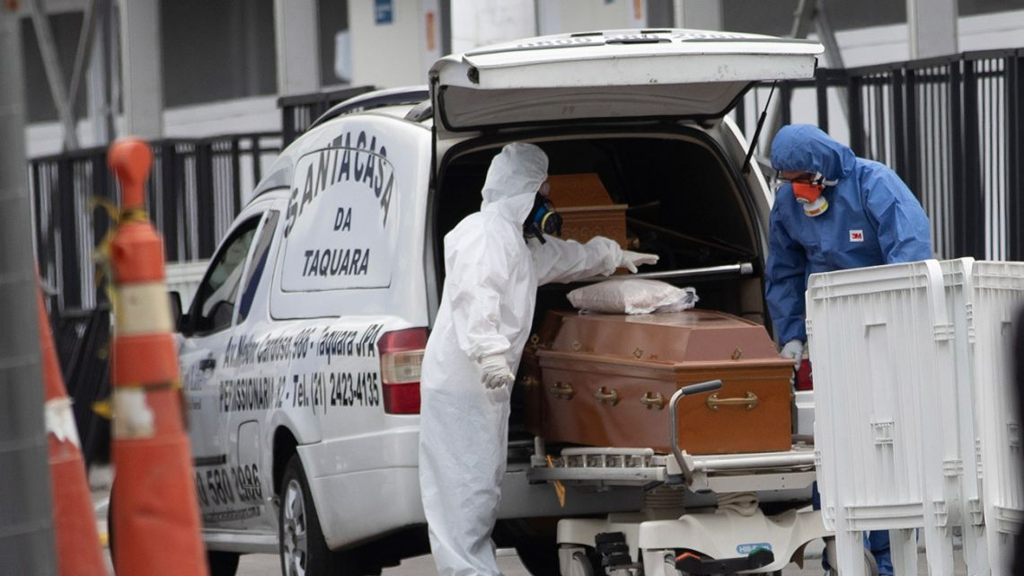 Funeral workers wearing protective gear as a precaution amid the new coronavirus pandemic push the remains of a Covid-19 victim into a funeral car at a field hospital in Leblon, Rio de Janeiro, Brazil, Thursday, June 4, 2020.