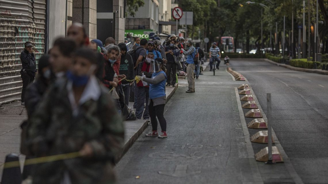 Volunteers sanitise the hands of people standing in line to receive food outside a church in Mexico City, Mexico, on Wednesday, June 3, 2020.