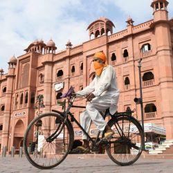 Un hombre sij monta una bicicleta a lo largo de la calle Heritage vacía después de que se impusieron estrictas normas de cierre durante los fines de semana y días festivos como medida preventiva contra el coronavirus COVID-19, en Amritsar.   Foto:NARINDER NANU / AFP