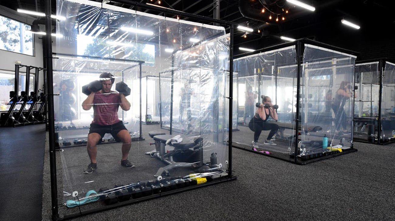 La gente hace ejercicio en Inspire South Bay Fitness, detrás del plástico en sus cápsulas de entrenamiento mientras cumple el distanciamiento social el 15 de junio de 2020 en Redondo Beach, California. El gimnasio reabre hoy bajo las pautas de la fase 3 del coronavirus.