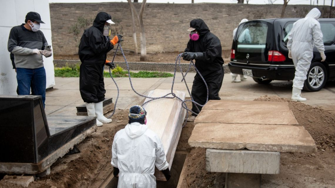 Workers lower the casket of a Covid-19 victim at a cemetery in Lima, Peru, on June 3.