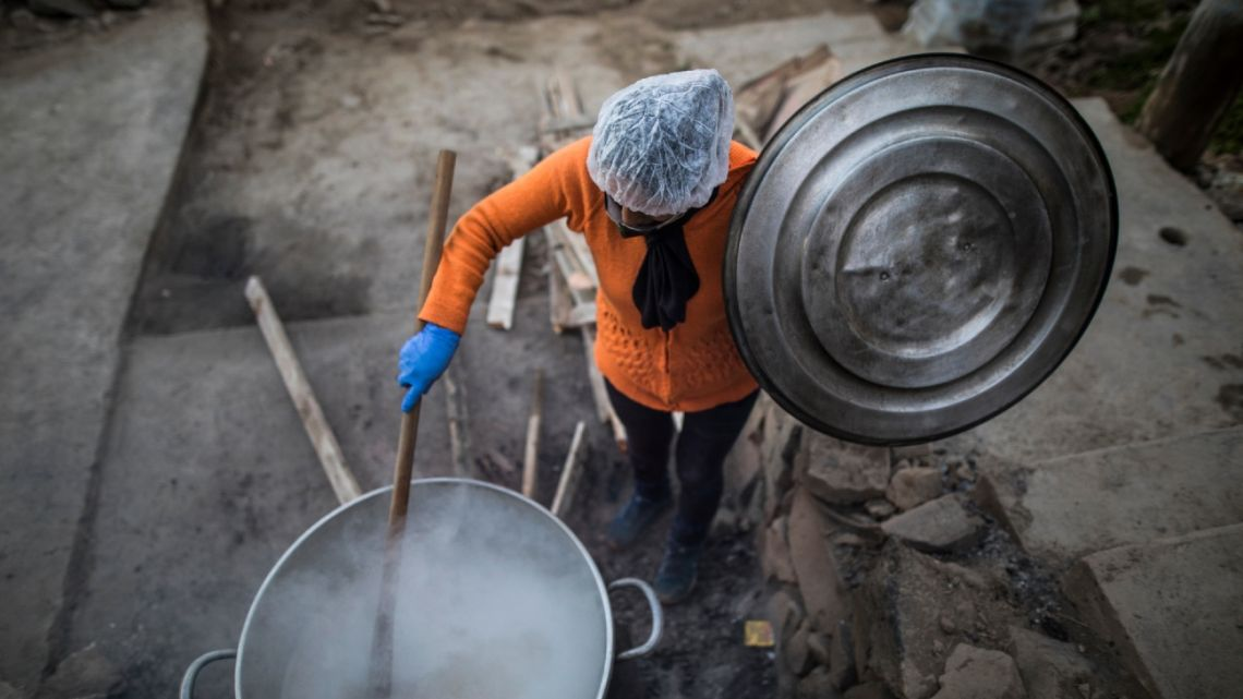 "Efraina Rivera stirs a vat of oatmeal at a ""community pot"" organised by residents in the Nueva Esperanza neighbourhood of Lima, Peru, Saturday, May 30, 2020."