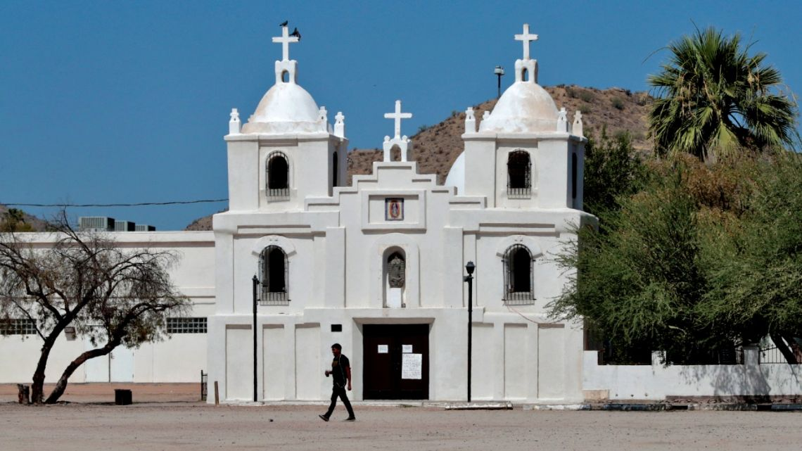 A man walks past Our Lady of Guadalupe church in Guadalupe, Arizona on June 13, 2020.