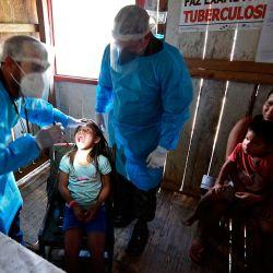 Los médicos de las Fuerzas Armadas de Brasil controlan a un niño indígena del grupo étnico Mayoruna, en la aldea de Cruzeirinho, cerca de Palmeiras do Javari, estado de Amazonas, norte de Brasil, en medio de la pandemia de COVID-19.   Foto:EVARISTO SA / AFP