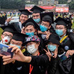 Esta foto muestra a los graduados universitarios con máscaras faciales que se toman una selfie durante su ceremonia de graduación en la Universidad de Wuhan en Wuhan, en la provincia central china de Hubei.   Foto:STR / AFP