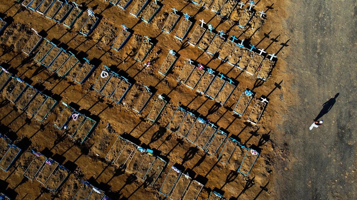 Aerial view showing a man walking past graves in the Nossa Senhora Aparecida cemetery in Manaus on June 21, 2020. The novel coronavirus has killed at least 464,423 people worldwide since the outbreak began in China last December, being Brazil Latin America's worst-hit country with 49,976 deaths from 1,067,579 cases.