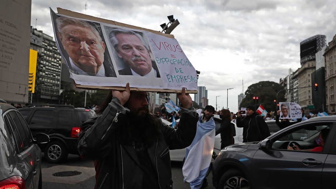"A man holds a sign with the images of Hungarian-US billionaire George Soros (left) and Argentina's President Alberto Fernández, reading ""Virus = expropriation of companies"" during a demonstration called by small businessmen affected by the government's mandatory quarantine imposed for more than 13 weeks, to protest against the quarantine and the expropriation of the Vicentin agro-industrial company on the Obelisk in Buenos Aires."