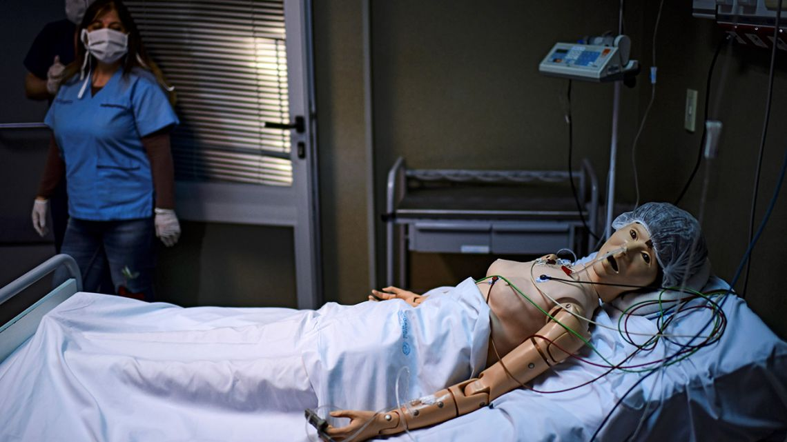 Argentine medical doctor Norma Raúl looks at a robot with which she practices medical assistance for Covid-19 patients, at the Clinical Simulation Training Center of the El Cruce hospital, in Florencio Varela, Buenos Aires Province.