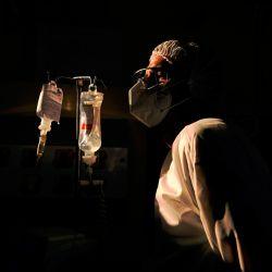 Un cirujano revisa el goteo intravenoso de uno de sus pacientes con COVID-19, en el hospital Oceanico en Niteroi, Río de Janeiro, durante la pandemia de coronavirus. | Foto:CARL DE SOUZA / AFP
