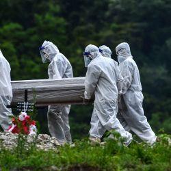 Hombres con trajes protectores llevan el ataúd de una presunta víctima del nuevo coronavirus en el cementerio Parque Memorial Jardín de los Ángeles. | Foto:ORLANDO SIERRA / AFP